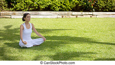 Lovely young woman meditating in the garden