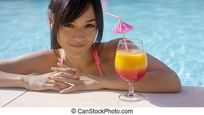 Happy young woman eyeing a large tropical cocktail