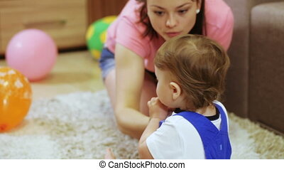 Child in room enjoys soap bubbles mom - On floor in sitting...