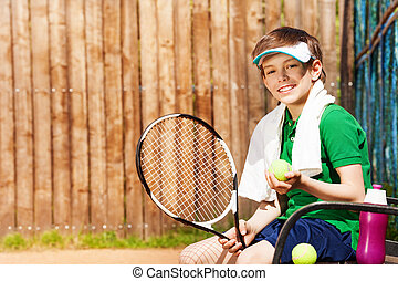 Young tennis player sitting on a bench after game