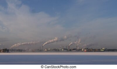 A factory with blowing smoke from the chimney near lake,...