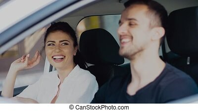 Cool couple having fun singing and dancing while driving car. Charming brunette woman and handsome man spending time together