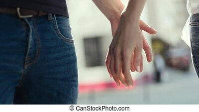 A pair of lovers wearing blue jeans join hands and walk together, close-up.