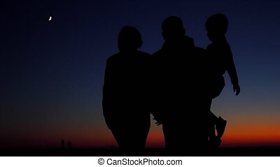 Happy family: father, mother and baby playing at sunset...