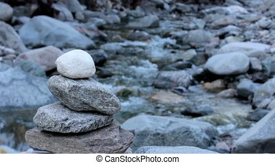 Stone cairn beside a river full hd