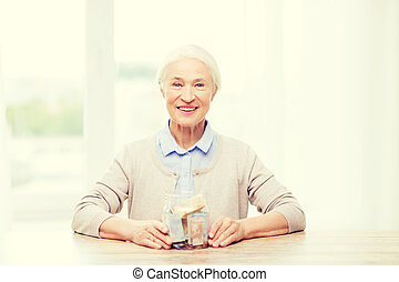 senior woman with money in glass jar at home - savings,...