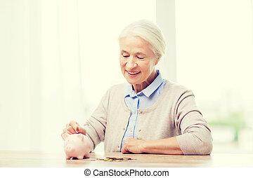 senior woman putting money to piggy bank at home - savings,...