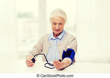 old woman with tonometer checking blood pressure - medicine,...