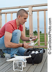 Young man setting drone in park Close up shot