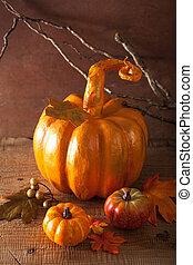 decorative golden papier-mache pumpkin and autumn leaves for...