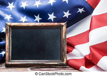 American flag on a wooden table and a blackboard