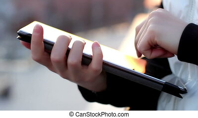 Close up of female hands using tablet computer on the balcony