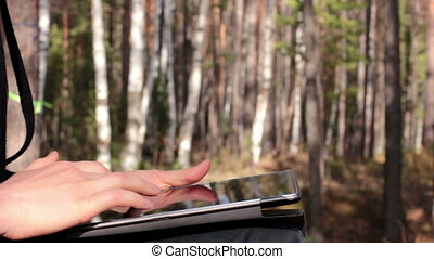 young woman uses a tablet pc in forest