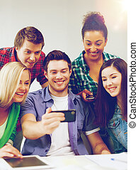 students looking into smartphone at school - education...