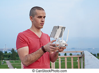 Young man operating a drone remote control console.