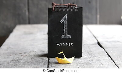 Winner, number one, lettering and yellow paper boat on a...