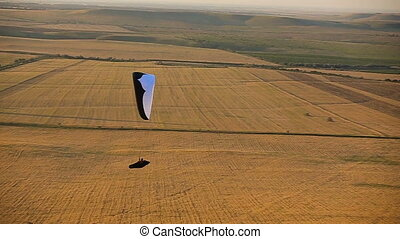 Paraglider in the sky over the steppe - Flying paraglider...