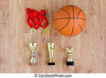 basketball ball with cups and golden medals