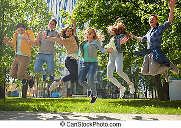 happy teenage students or friends jumping outdoors -...