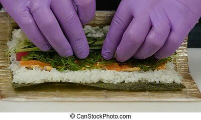 Chef uses a bamboo mat for preparing sushi. Close up - Male...
