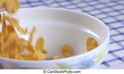 Breakfast cereal tasty cornflakes falling into bowl in slow...