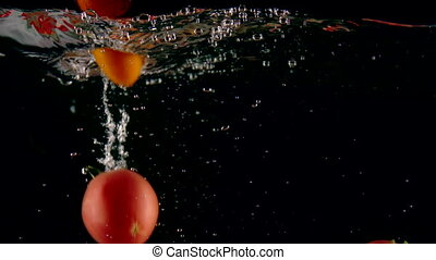 Ripe red and yellow tomatoes falling into clear water with...