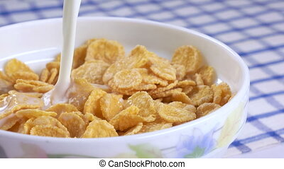 Breakfast cereal pouring milk into bowl of corn flakes in...
