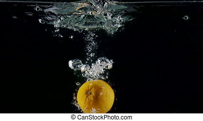 Fresh fruit orange falling into water with splash on black background