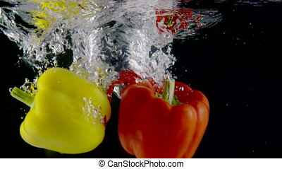 Two yellow red sweet bell peppers falls into clear water slow motion