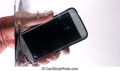 Smart phone in hand punching the water surface with splash...