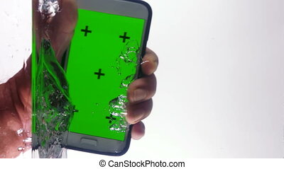 Smart phone with green screen in hand punching water surface...
