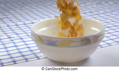 Breakfast cereal crunchy corn flakes falling into bowl in...