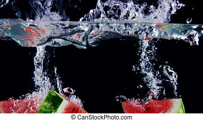 Fresh ripe watermelon slices falls into water with splashes...