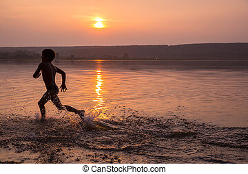 Boy running on river's beach against sunset