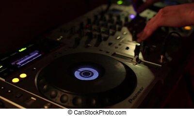 Hands of DJ tweak various track controls on dj's deck,...