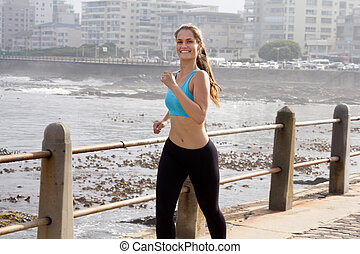 Keeping Fit - A fit woman running on the Promenade and...