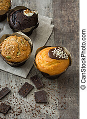 Chocolate muffins on a rustic wooden table