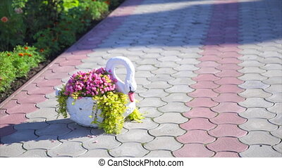 decorative swan with flowers on the yard
