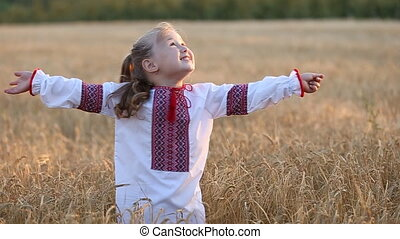 little girl walks on a wheat field in Ukrainian natsyonalnoy...