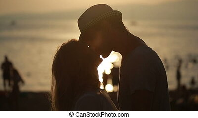 silhouetted couple hold each other and kiss on the beach...