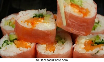 Chef puts sushi in pink norrie in a bowl Close up - Rolls...