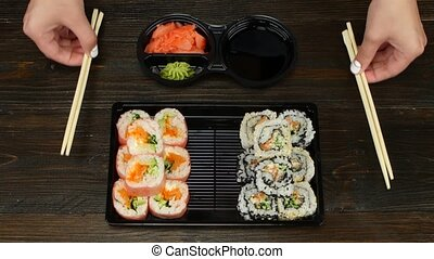Rolls ready for catering Sushi in plastic dishes Close up -...
