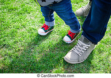 Walking toddler concept - First steps. Baby learning to...