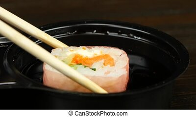 Person prepares the roll for eating Close up - Peole puts...