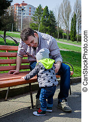 Toddler and father outside - Baby learning to stand with...