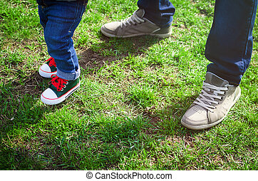 Walking toddler concept First steps Foot of father and son...
