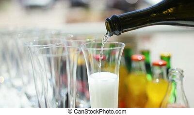 Bottle filling champagne flute against black background
