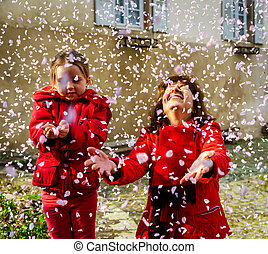 Mother with little daughter playing with falling petals...
