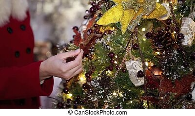 woman shopping christmas decorations for tree in market...