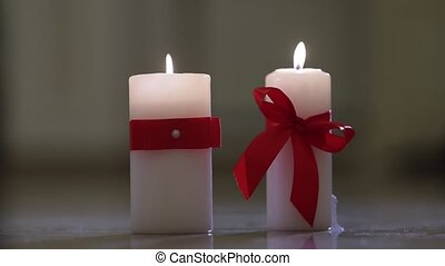 white candle with red bow